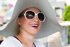 Woman in Hat and Sunglasses Laughing Outdoors Royalty Free Stock Photography