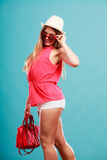 Woman in hat sunglasses and red shirt with handbag Royalty Free Stock Images