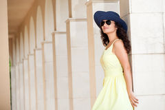 Woman with hat, sunglasses and yellow dress Royalty Free Stock Image