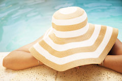 Woman with hat in swimming pool Stock Photo