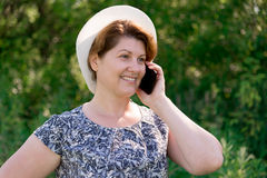 Woman in hat talking on cell phone outside Stock Images