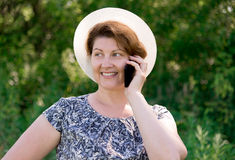 Woman in hat talking on cell phone outside Stock Photos
