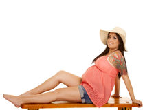 Woman hat tattoo pink shirt sit side look Royalty Free Stock Photography