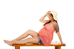 Woman hat tattoo pink shirt sit side Stock Images