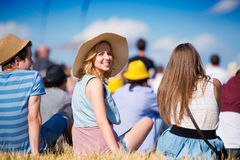 Woman with hat, teenagers, summer festival, sitting on grass Stock Photo