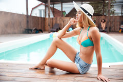 Woman in hat thinking and sitting near swiming pool Stock Images