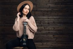 Woman in a hat with a ukulele indoors on a wooden wall background stock image