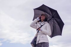 Woman with hat and umbrella talking on the phone Stock Photography