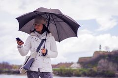 Woman with hat and umbrella talking on the phone Royalty Free Stock Images