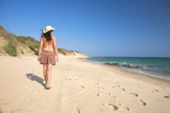 Woman with hat walking beach Royalty Free Stock Photos