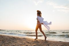 Woman with hat walking at the beach. Picture of pretty young woman with hat walking outdoors at the beach Stock Photos