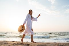 Woman with hat walking at the beach. Picture of pretty young woman with hat walking outdoors at the beach Royalty Free Stock Photography