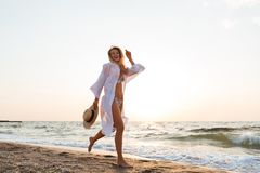 Woman with hat walking at the beach. Picture of pretty young woman with hat walking outdoors at the beach Royalty Free Stock Photo