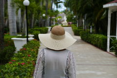 Woman in hat walking in Paradise on a beautiful day royalty free stock photography