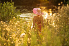 Woman with hat on the waterfront on a summer evening Royalty Free Stock Photo