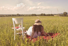 Woman with Hat and White Dress on Picnic Blanket. Woman with Hat in White Dress is Looking to Distance on Red Picnic Blanket Royalty Free Stock Photos
