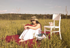 Woman with Hat and White Dress on Picnic Blanket. Woman with Hat in White Dress is Reading a Book on Red Picnic Blanket Stock Image