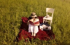 Woman with Hat and White Dress on Picnic Blanket. Woman with Hat in White Dress is Reading a Book on Red Picnic Blanket Stock Images