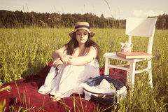 Woman with Hat in White Dress on Picnic Blanket. Woman with Hat in White Dress is Sitting on Red Cloth on Green Meadow with White Chair and Picnic Basket Royalty Free Stock Image