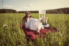 Woman with Hat in White Dress on Picnic Blanket. Woman with Hat in White Dress is Sitting on Red Cloth on Green Meadow with White Chair and Picnic Basket Stock Image