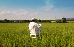 Woman with Hat in White Shirt is Sitting on White Chair. Woman with Hat and White Shirt is Sitting on White Chair on Meadow in Sunset with Time Clock-Waiting Stock Images
