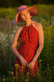 Woman in a hat among wildflowers at sunset Royalty Free Stock Photo
