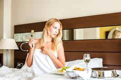 Woman have breakfast in badroom in hotel. Beautiful young adult blond Woman model have breakfast dinner or lunch in badroom in hotel stock images
