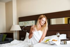 Woman have breakfast in badroom in hotel. Beautiful young adult blond Woman model have breakfast dinner or lunch in badroom in hotel stock photo