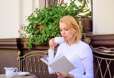 Woman have drink cafe terrace outdoors. Bookworm leisure concept. Mug of good coffee and pleasant book best combination. For perfect weekend. Girl drink coffee royalty free stock photo