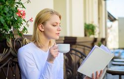 Woman have drink cafe terrace outdoors. Find opportunity to read more. Girl drink coffee while read bestseller book by. Popular author. Mug coffee and royalty free stock images