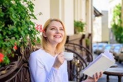 Woman have drink cafe terrace outdoors. Reading is her hobby. Mug coffee and interesting book best combination perfect. Weekend. Girl drink coffee while read royalty free stock photography