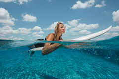 Woman have fun in outdoor infinity pool. Positive girl swimming with surf and relax at poolside Stock Photos
