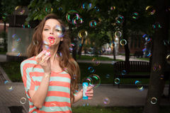 Woman have fun with soap bubbles in summer park Stock Images
