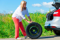 Woman have prepared to replace the spare wheel Royalty Free Stock Image
