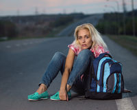 Woman with haversack sitting on the road. Woman hitchhiking on the road Royalty Free Stock Photography