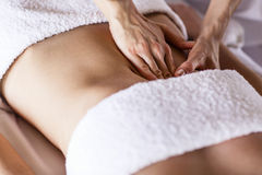 Woman having abdomen massage. Beautiful young woman having visceral massage in spa center Royalty Free Stock Image