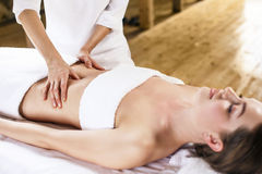 Woman having abdomen massage. Beautiful young woman having visceral massage in spa center Stock Photo