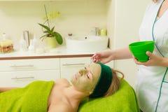 Woman having algae mud mask on face Stock Photography
