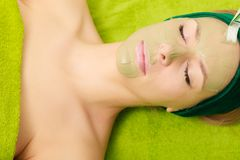 Woman having algae mud mask on face. Someone applying woman green algae mud mask on face. Beauty, relaxation, skincare, wellness in spa concept Royalty Free Stock Photo