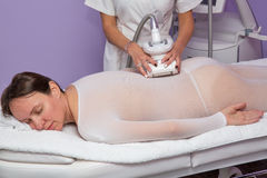 Woman having anti cellulite massage with apparatus. Woman in the white special suit having anti cellulite massage with apparatus Royalty Free Stock Image