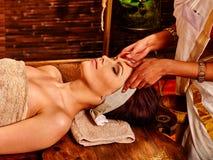 Woman having ayurveda spa treatment. Woman having facial ayurveda spa treatment. Wooden brown bed royalty free stock image