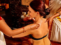 Woman having ayurveda spa treatment. Young woman with bare back having ayurveda spa treatment stock images