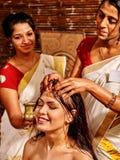 Woman having ayurveda spa treatment. Young women having head ayurveda spa treatment. Two masseuses stock photos