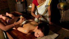Woman having ayurvedic back massage with pouch of rice. One can see only hands  of Indian masseuses. stock video