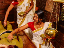 Woman having Ayurvedic body  spa massage. Young woman having body Ayurveda spa massage. Two therapist Stock Photos