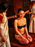 Woman having Ayurvedic spa treatment with pouring massage oil. Stock Photography