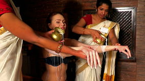 Woman having Ayurvedic spa treatment. Two real Indian masseuse  are pouring oil  of patient. stock footage