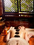 Woman having Ayurvedic stone massage. Stock Photos