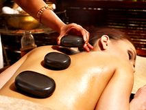 Woman having Ayurvedic stone massage. Royalty Free Stock Images