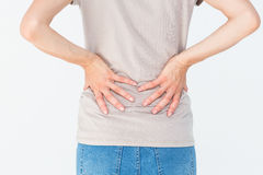 Woman having a back ache and holding her back Royalty Free Stock Image